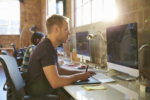 Designers Working At Desks In Modern Office