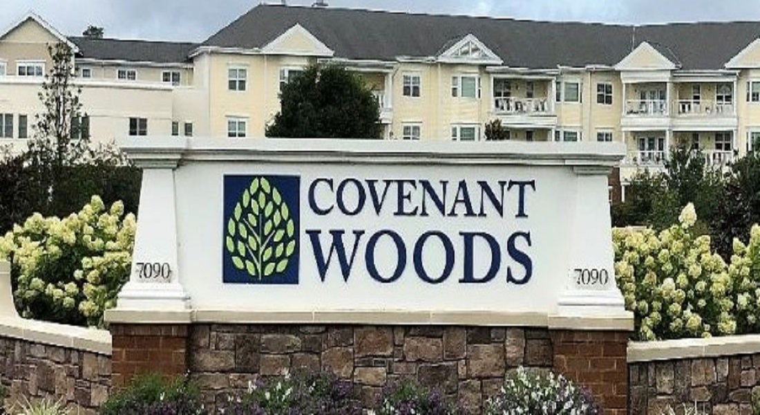Covenant Woods sign and buildings in the background