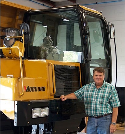 Ken Byrd, President of Morooka USA standing next to a large rubber track carrier that they built
